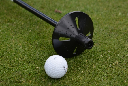 golf ball lifter on practice putting green flag