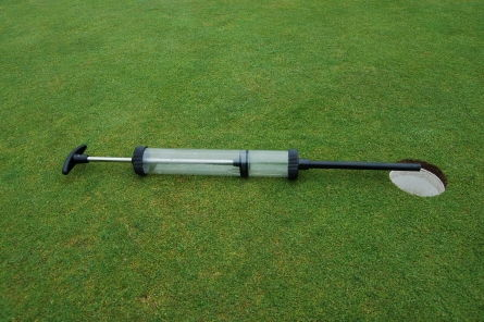 hole cup syringe on golf green