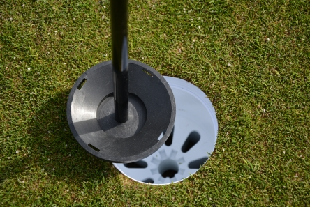 putting green flag with plastic ball tray in standard golf hole cup