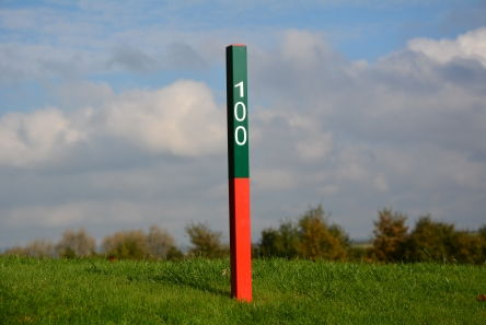 red and green 100 fairway distance post